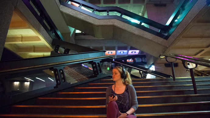 Photo of woman sitting on stairs listening to headphones