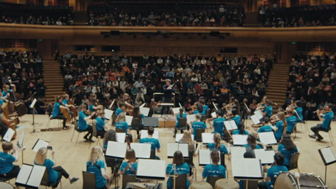 Photo of young people playing in an orchestra in the Barbican Hall