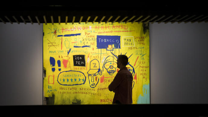 Photo of man looking at Basquiat paintings in the Barbican Art Gallery