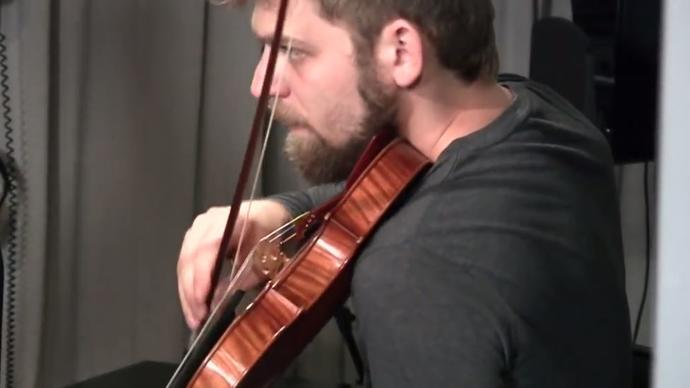 a still of a man playing the violin