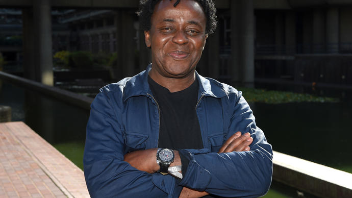Photo of artist John Akomfrah by the Barbican lakeside