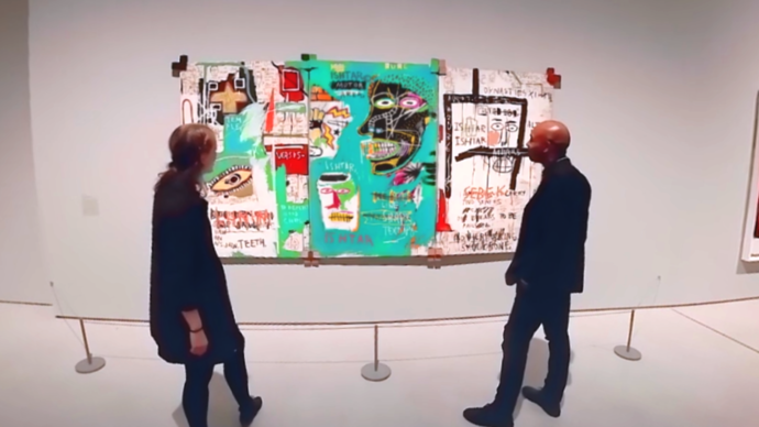 Photo of two people looking at Basquiat painting