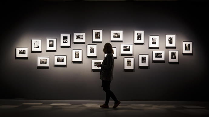 Silhouette of woman looking at photographs