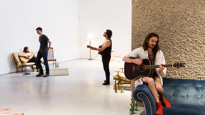 Group of men playing guitar sitting on sofas in the Barbican Art Gallery