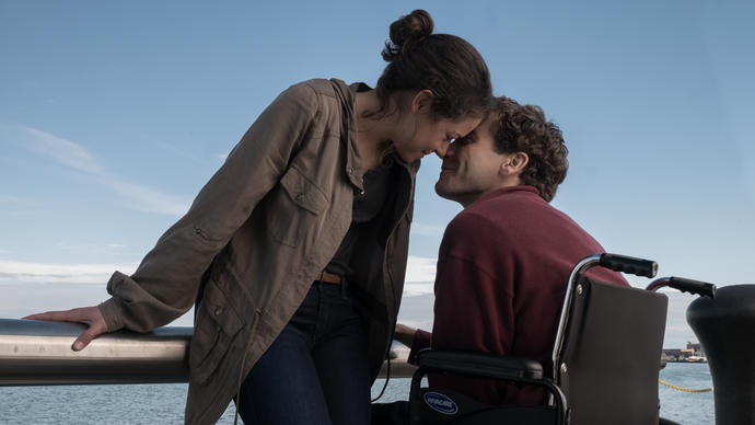 photo of a woman kissing a man in a wheelchair