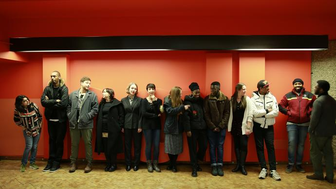 13 people standing in a line along an orange wall, talking and laughing