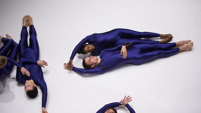 Photo of dancers lying on the floor in blue leotards
