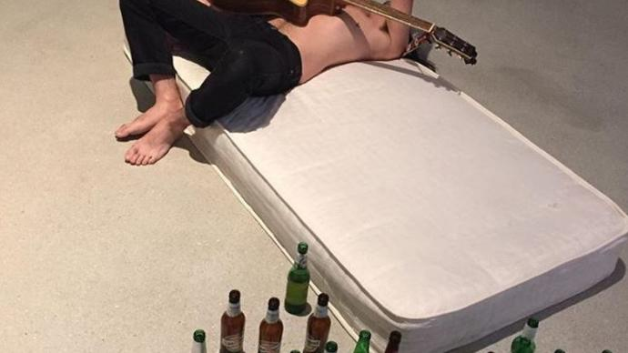 Man on mattress with beer bottles