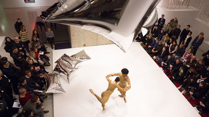 Two dancers perform with silver balloons in an art gallery