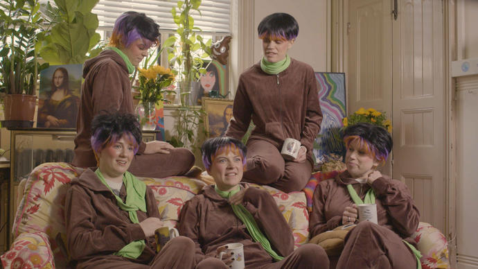 Group of five women sitting on a sofa wearing brown jumpsuits and wigs