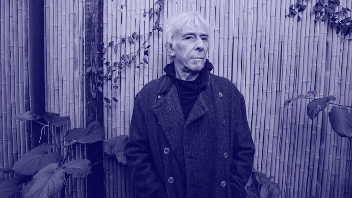 Photo  of John Cale standing in front of a bamboo wall
