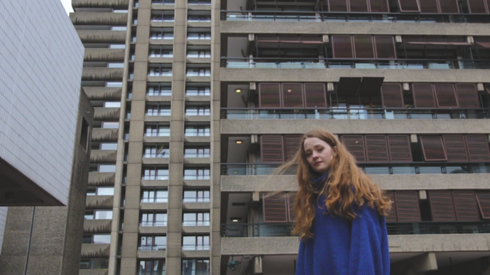 photo of young poet laurie ogden standing in front of barbican towers