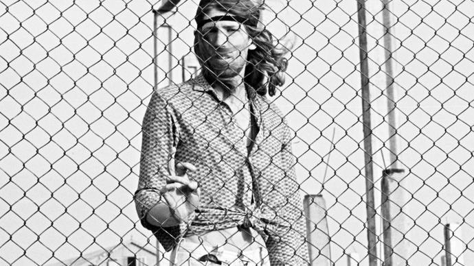 Photo of man with long hair behind a fence