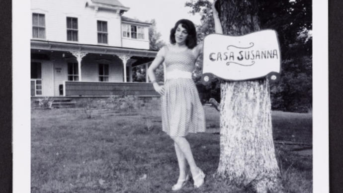 Black and white photo of person standing by a Casa Susanna sign