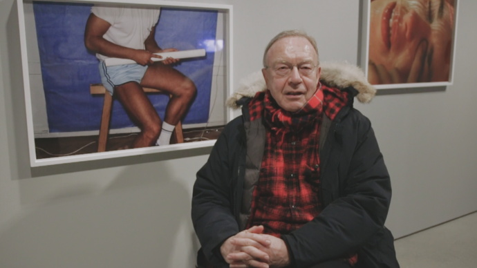 photo of swiss photographer walter pfeiffer in front of his own photos