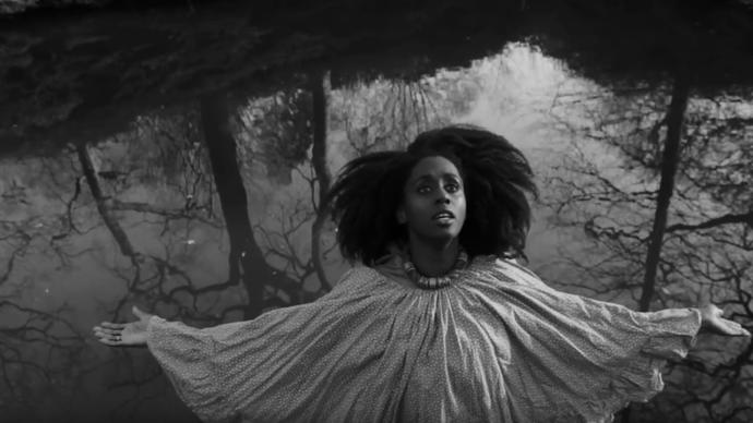 black and white photo of lady vendredi performing in the woods
