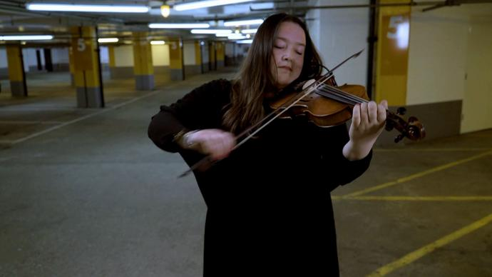musician laura cannell performing in a car park