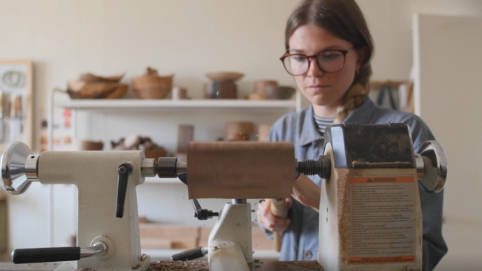 photo of elise mclaughlan turning wood with a wood machine