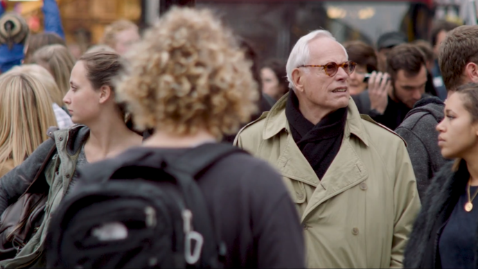 photo of an old man wearing a trench coat standing in a crowd of people