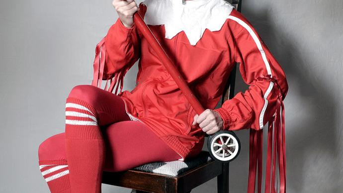 Gazelle Twin wearing a jester costume with a hobby horse, seated on a chair
