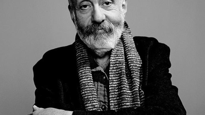 black and white photo of mike leigh in a black blazer and a scarf