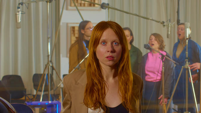 Holly Herndon in front of a choir recording