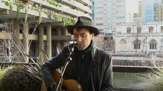 photo of andrew bird with a black hat by the barbican lakeside