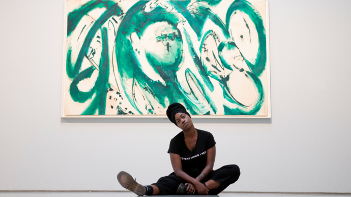 image of young poet anita barton-williams sitting on the floor in front of a green painting by lee krasner