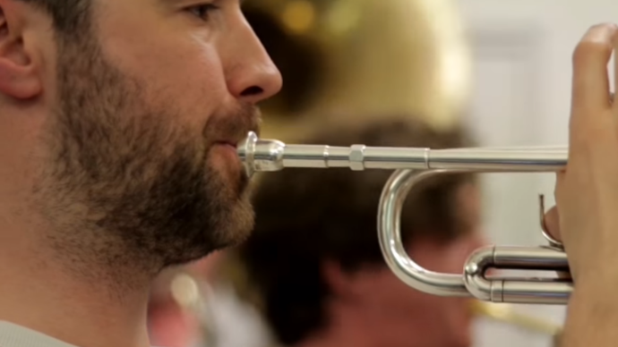 Close up photo of a  man playing the trumpet