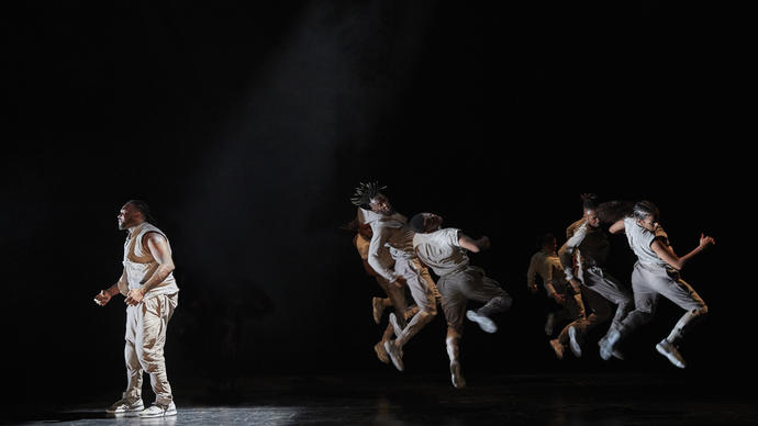A dancer is looking anguished in the spotlight, while behind them other dancers jump in the air in unison