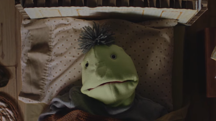photo of a puppet laying on it's bed whilst looking directly at the camera.