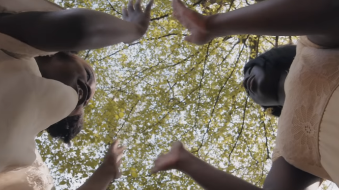 Low angle looking up at two young girls clapping their hands together