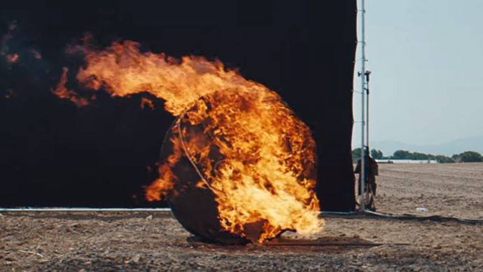 Photo of a black circular object on fire, in the middle of a field