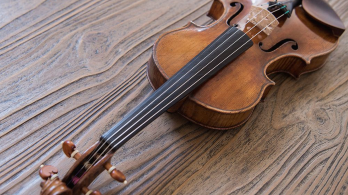 Photo of a violin laying on a wooden table