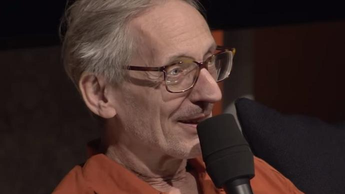Photo of Manuel Göttsching talking into a microphone, wearing a orange shirt and glasses