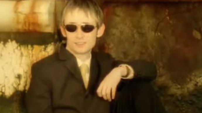 Photo of a man sitting posing towards the camera with black glasses and suit