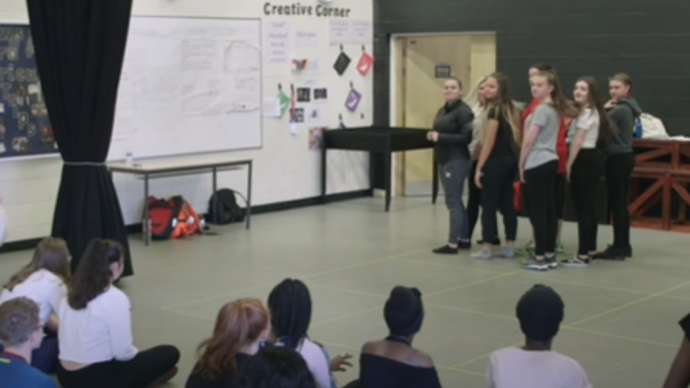Group of teenagers performing to their class mates
