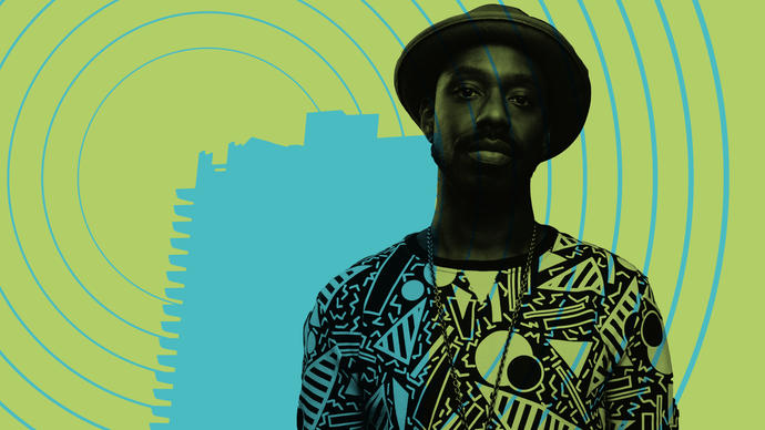 Shabaka Hutchings with a silhouette of the Barbican behind him