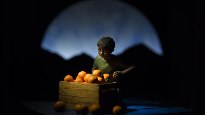 Photo of a boy sitting by a box of oranges