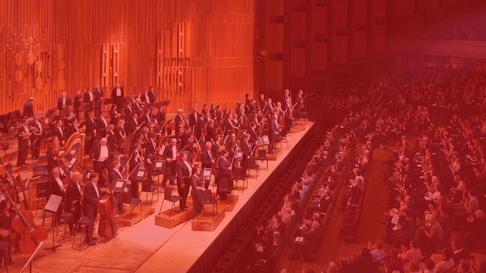 an orchestra playing classical music in the barbican hall in central london