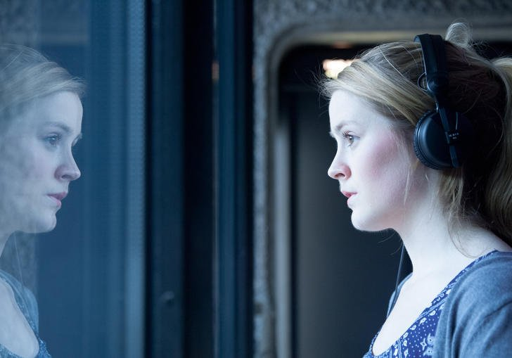 Photo of woman wearing headphones looking out of a window