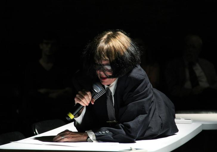 Photo of a woman in glasses using a mic. She is lying on a table.