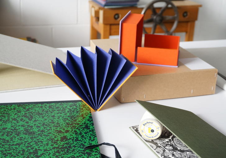 Detail of bookbinding workshop showing handmade notebook