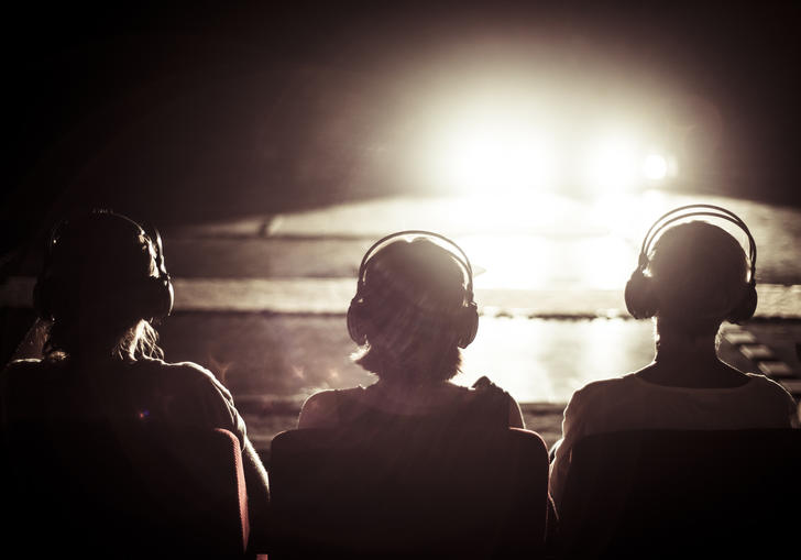 Image of three people with headphones looking into a bright light