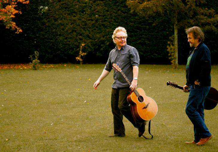 Andy Irvine and Paul Brady carrying a couple of guitars enjoying a walk on some very green grass