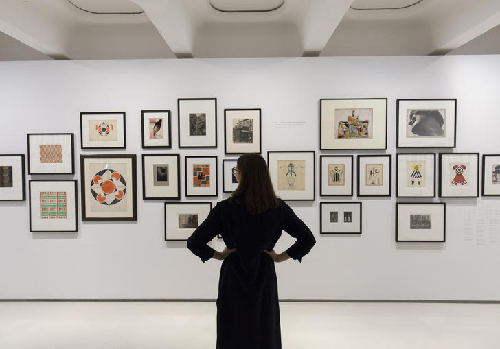 A woman looks at a selection of art, they're from the exhibition Modern Couples. She seems to be enjoying herself, encouraging the viewer to book tickets