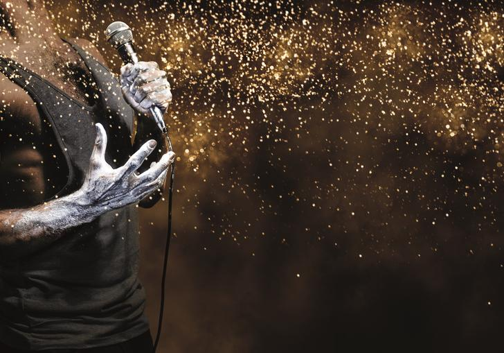 zoomed in image of a man's chest with a vest on. One hand grips a mic and the image is full of glitter
