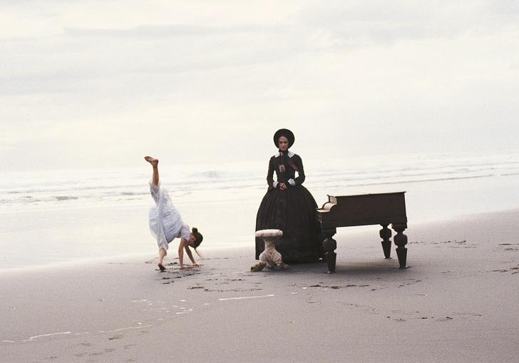 A scene from The Piano. A child does a handstand and a woman sits at a piano on a beach