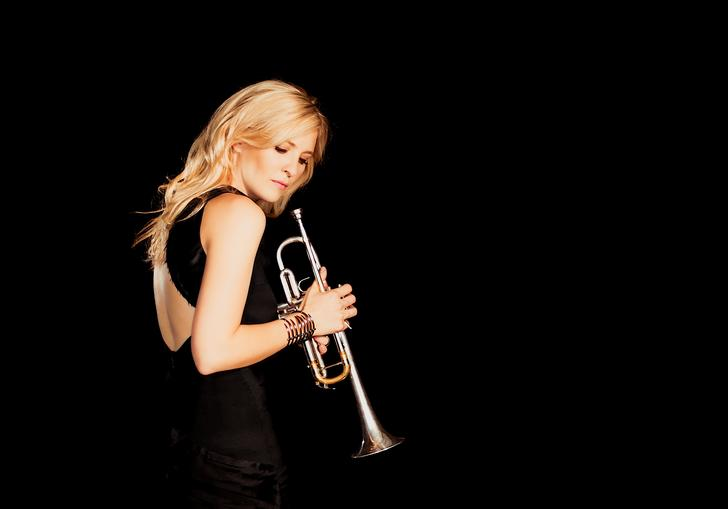 Alison Balsom holding trumpet black background