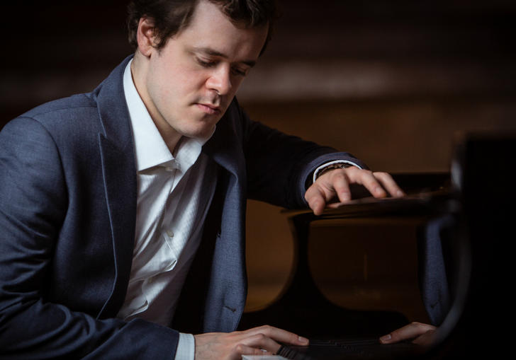 Benjamin Grosvenor sitting at a piano 2019